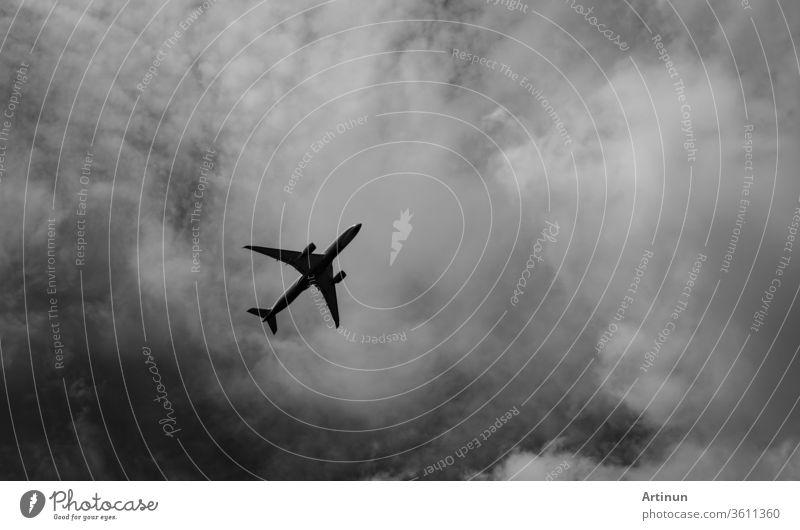 Verkehrsflugzeug am grauen Himmel und Wolken mit Kopierraum. Gescheiterter Urlaub. Hoffnungsloses und verzweifeltes Konzept. Launischer Himmel und Transportflugzeug. Traurig-emotionale Szene. Hintergrund des Flugzeugflugs.