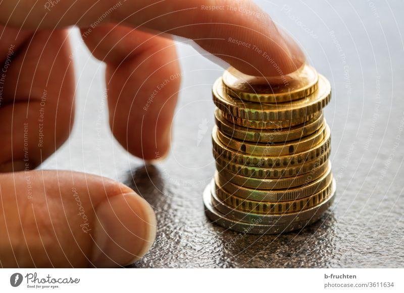 Ein Stapel Euro-Münzen münzen Geld Bargeld Geldmünzen bezahlen sparen Einkommen Kapitalwirtschaft Wirtschaft Investition Hand Finger Zeigefinger halten