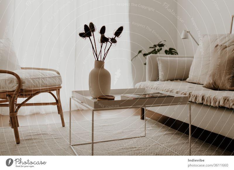 Sonnenbeschienenes Wohnzimmerinterieur mit Rattansessel, weißem Couchtisch und weißem Sofa mit Kissen und Decke, Vase mit Trockenblumen, Palmblättern, Lampe, Zeitschriften und Teppich.