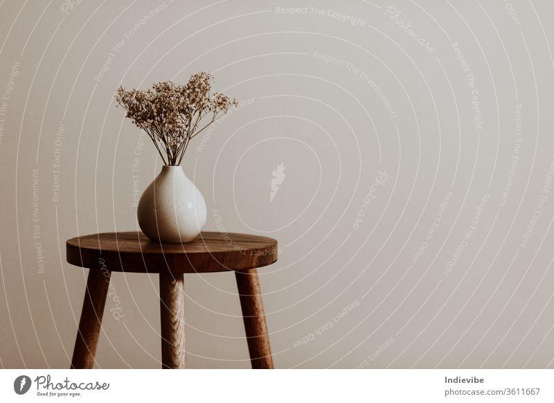 Weiße Keramikvase auf einem naturbraunen Holzhocker mit weißen Trockenblumen in einem leeren Raum Hocker Innenbereich Dekoration & Verzierung Design hölzern