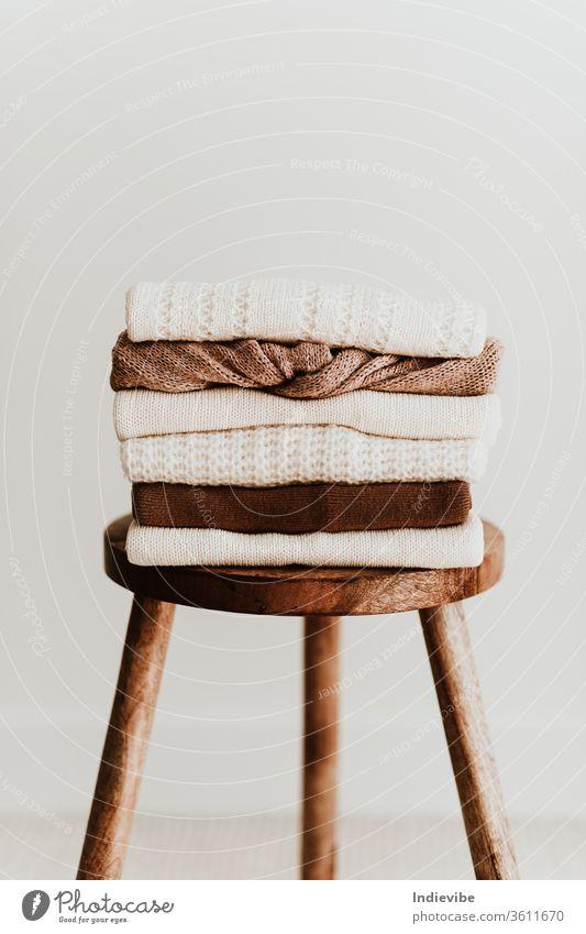 Zusammensetzung der Damenmode. Warme weibliche Strickpullover aus Wolle für den Winter, Pullover stapeln sich auf einem Holzhocker auf weißem Hintergrund. Modernes Kleidungskonzept für Zeitschrift, Blog, soziale Medien.