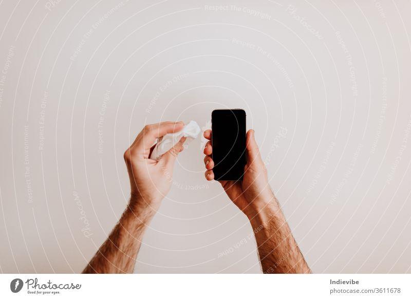 Handreinigung eines Telefonbildschirms mit antibakteriellen Feuchttüchern, um eine Viruskontamination zu vermeiden. Mobile Smartphone Finger benutzend klug