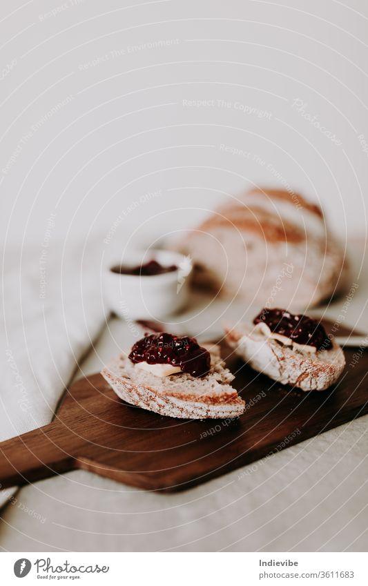 Zwei Scheiben hausgemachtes Bio-Sauerteigbrot mit Butter und Himbeermarmelade auf einem Holzschneidebrett mit Löffel und Laib Brot und Serviette. Gesunde Frühstücksidee für Vegetarier