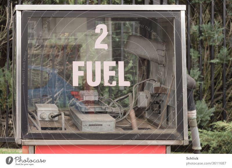 Alte marode Zapfsäule für Flüssigtreibstoff im Detail mit Spiegelbild eines blauen ach so umweltfreundlichen xyz Autos fuel Text Spiegelung Zukunft