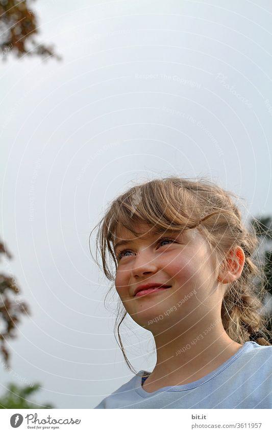Blondes, natürliches, fröhliches Mädchen steht lächelnd und zufrieden, draussen in der Natur, zwischen grünen Bäumen, vor bedecktem Himmel. Glückliches, strahlendes Mädchen, bei Familienausflug im Frühling, mit wehenden Haaren in der hellen Umgebung..
