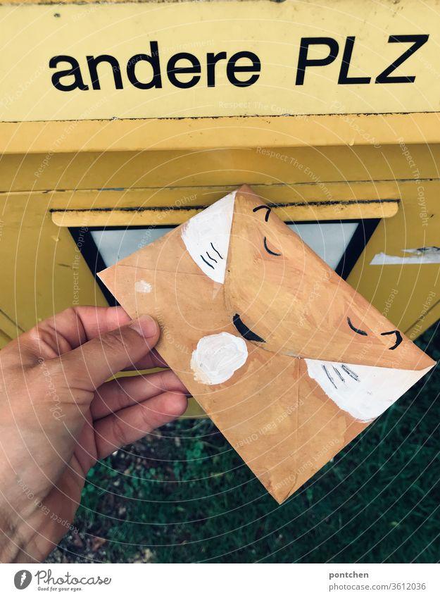 Hand wirft einen als Fuchs bemalten umschlag in den BriefSchlitz für andere Postleitzahlen des Briefkasten. Einladung zum Kindergeburtstsg Beschriftung