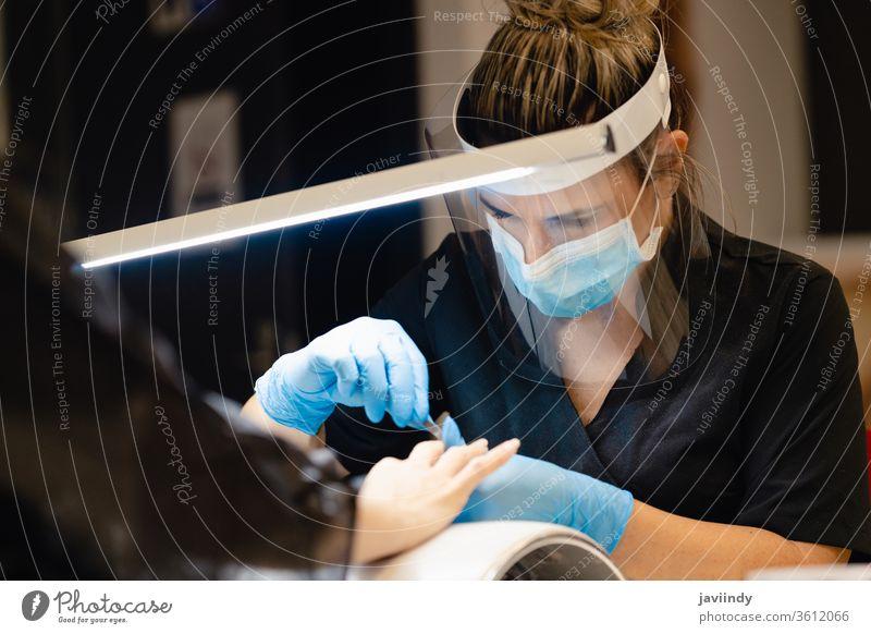 Ästhetiker, der die Maniküre macht, feilt die Nägel mit einer Feile seiner Kundin in einem Schönheitszentrum Aktenordner nageln Nagellack Fingernagel Frau Salon