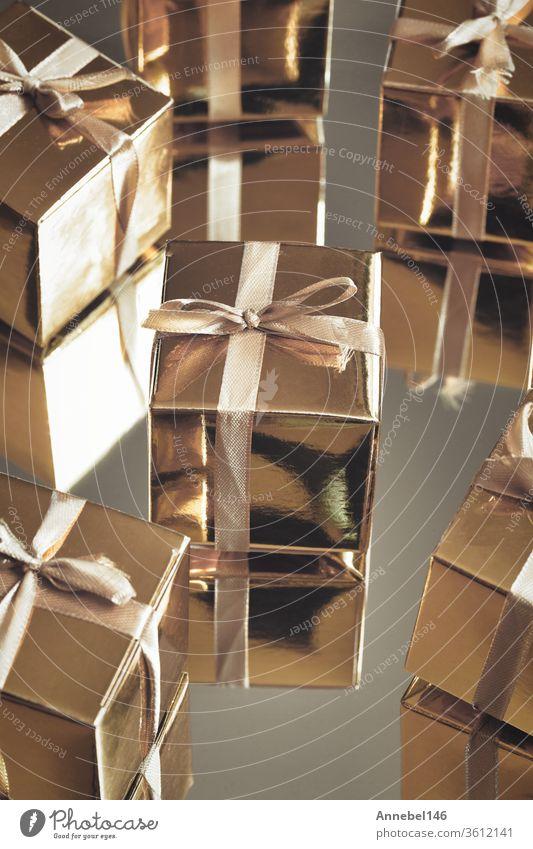 Gruppe von goldfarben glitzernden Geschenkschachteln auf grauem Hintergrund mit Spiegelung. Gruppe von goldenen Geschenkschachteln für Geschenk, Überraschung, Geburtstag, Weihnachten Konzept
