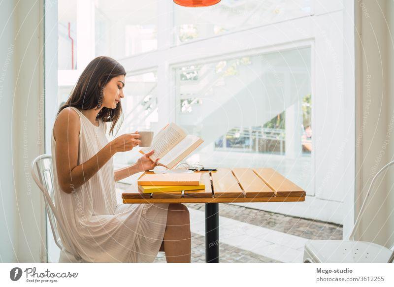 Junge Frau liest in einem Café ein Buch. Sitzen lesen Werkstatt Kaffee entspannend Hobby ernst Kultur Kaffeepause Kaukasier Blick besinnlich Lehrbuch Porträt