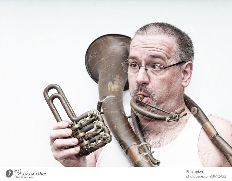 Schielender Mann im Unterhemd mit kaputtem Tenorhorn freigestellt Blechblasinstrument Horn Brille schielen Bart Brillenträger Erwachsene Spaßvogel Porträt