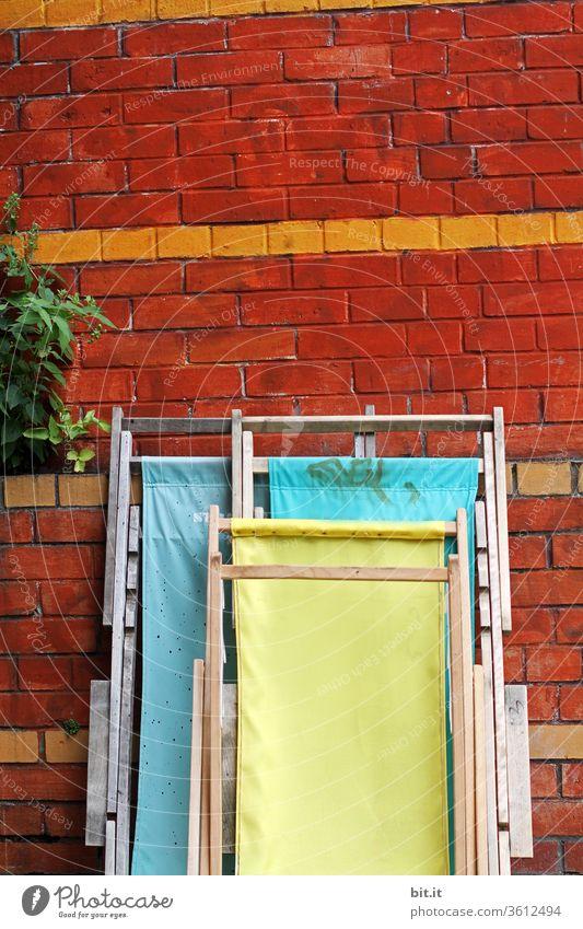 Drei einsame Liegestühle stehen zusammengeklappt, vor einer Wand aus Backstein und warten auf den Saisonanfang. Geschlossene, bunte Holzliegen lehnen ordentlich aufgeräumt an einer Wand mit Pflanze. Strandhaus im Sommer mit gelben & türkisen Stoffliegen.