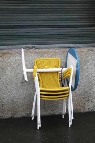 Gelbe, knallige, poppige Bistrostühle aus Plastik stehen aufeinander gestapelt, vor grauer, trister Hauswand, mit geschlossenen Rollläden. Feierabend, Saisonende in Straßencafe mit übereinander gestapelten Möbeln, Stühlen und blauem, runden Bistrotisch. Zu