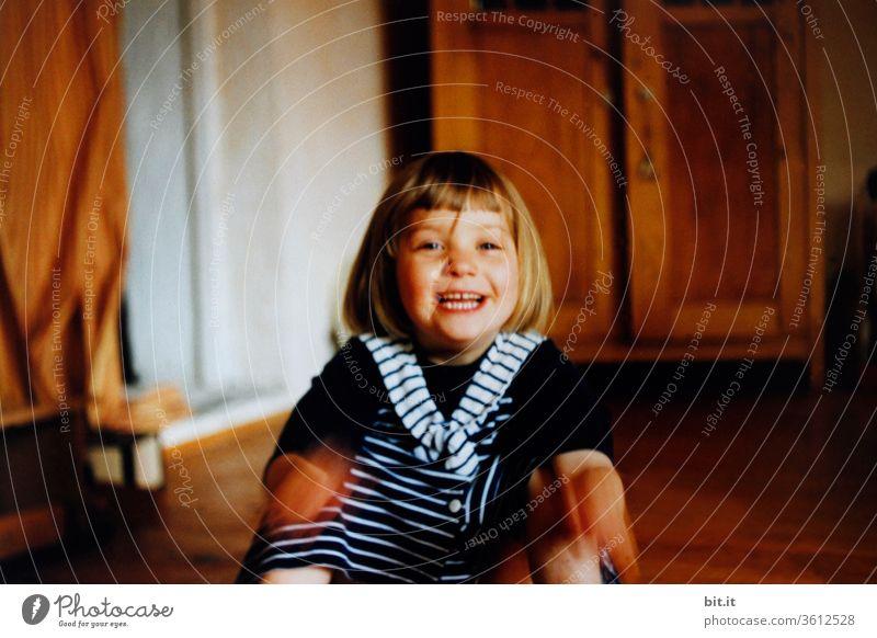 Lustiges, kleines Mädchen lacht laut mit offenem Mund zuhause in der warmen, holzigen Wohnung. Witziges, ulkiges, lachendes Kleinkind macht Blödsinn. Ulknudel, Spaßvogel macht Quatsch und sitzt daheim auf braunem Holzboden. Fröhliche, glückliche Kindheit.