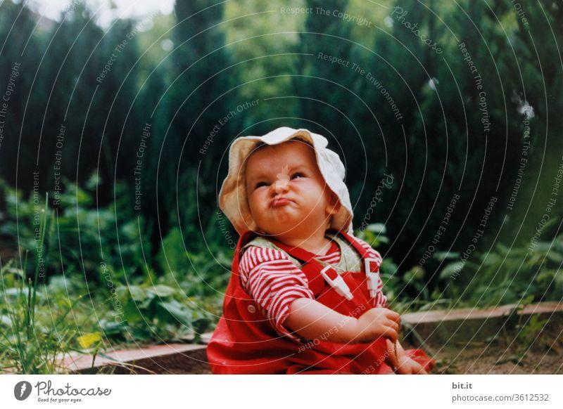 Kleines Mädchen sitzt mit roter Matschhose und Mütze mit Rüschchen, im Sandkasten vom Garten, mit grüner Hecke hinten. Das Kind zieht eine süße, lustige, niedliche Schnute und schaut witzig, neugierig, interessiert, nach oben in die Luft. Regentag zuhause.