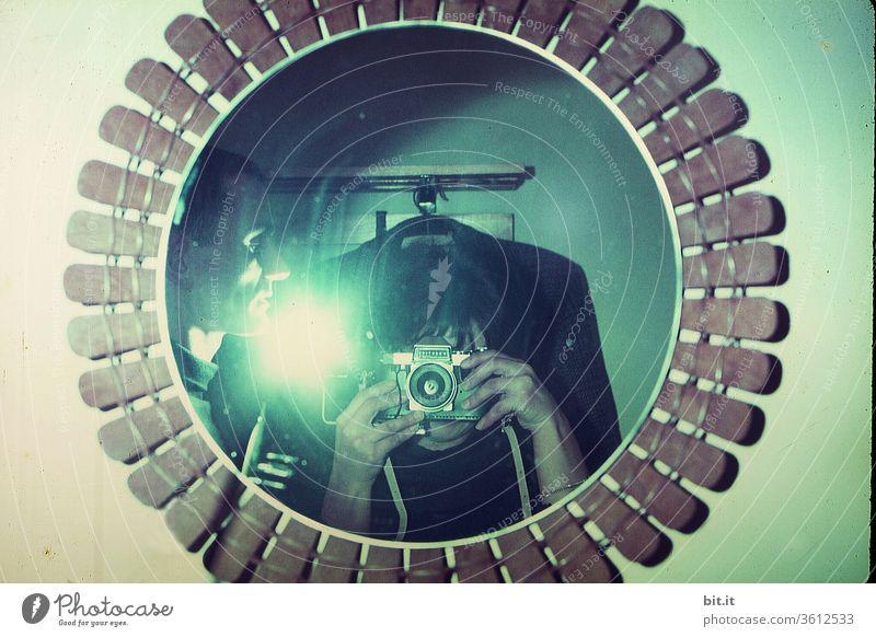 alt l junges, neugieriges Paar, fotografiert im Spiegel mit Blitzlicht. Interessierter Mann und Frau experimentieren mit Blitzlicht, alter Kamera und Spiegelbild. Fotokunst mit Selfie, Lichtstrahlen, Blitzeffekt, Belichtung, Beleuchtung, Lichtfotografie.