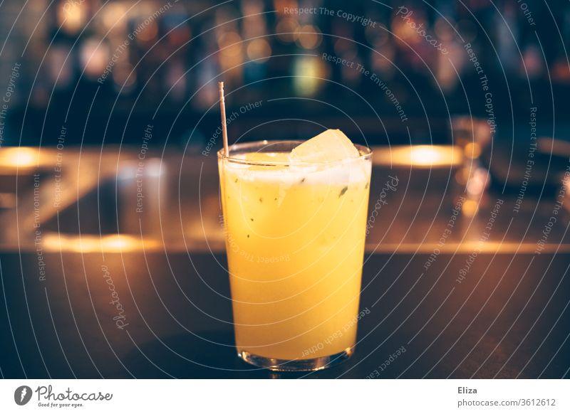 Ein Cocktail auf dem Tresen einer Bar Drink Limonade Getränk orange Eiswürfel abends Alkohol ausgehen Erfrischungsgetränk Longdrink Glas Cocktailbar lecker