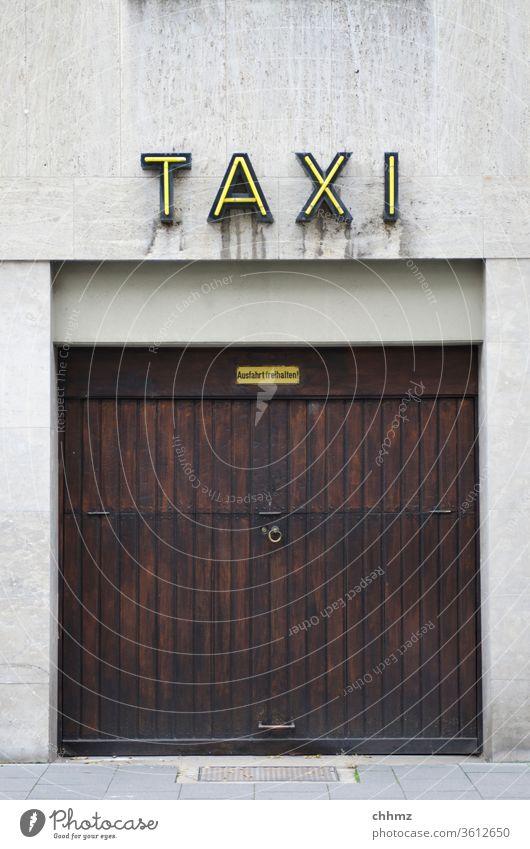 Taxigarage Garage Schild Leuchtreklame Verkehr Außenaufnahme Garagentor Gebäude Fassade Stadtzentrum Einfahrt Mauer Ausfahrt Wand Schriftzeichen Tor