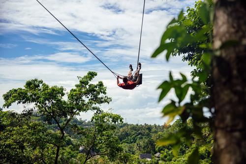 Junger männlicher Tourist schwingt sich auf der Klippe im Dschungel Adrenalin Abenteuer Bali schön Eruption extrem Freiheit Spaß lustig grün Indonesien Insel