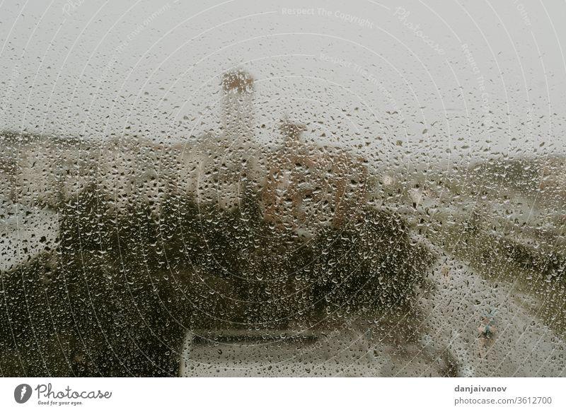 Nasses Fenster vor dem Hintergrund eines abendlichen Ausblicks auf die Stadt Regentropfen Wasser abstrakt nass Textur Natur Glas Wetter regnerisch aqua