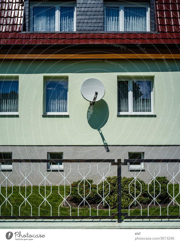 Satellitenschüssel an Hauswand Architektur Gebäude Fenster Fassade Menschenleer Außenaufnahme Wand Mauer Zaun Grün Rot Fernsehempfang Farbfoto blau Schatten