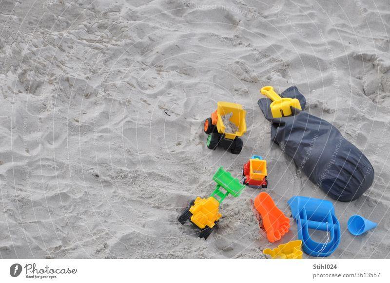 Spielzeugautos und Spielzeug aus Plastik am Sandstrand Strand Vogelperspektive Auto LKW Lastwagen spielen Sommer Sandkasten HArke Förmchen Sandspielzeug sandeln