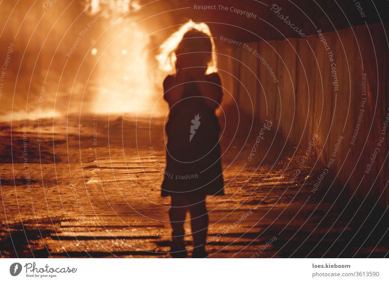 Defokussierte Silhouette eines Kindes, das sein Gesicht mit den Händen bedeckt, und verschwommene Person, die hinten ins Licht läuft Missbrauch Gewalt Opfer