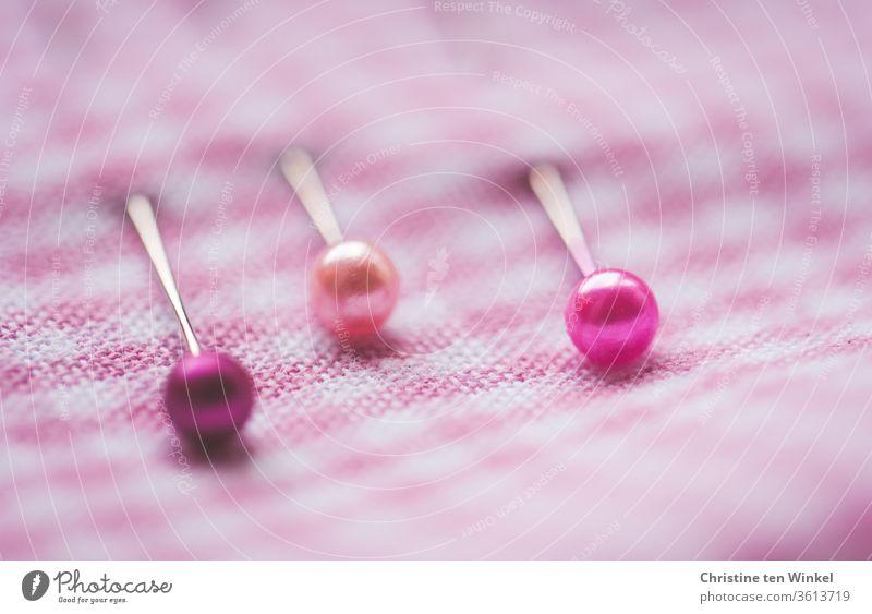 Drei Stecknadeln mit pinkfarbenen Köpfen halten den pink und weiß kleinkarierten Stoff zusammen Stecknadelkopf Vichykaro karierter Stoff rosa mädchenfarben