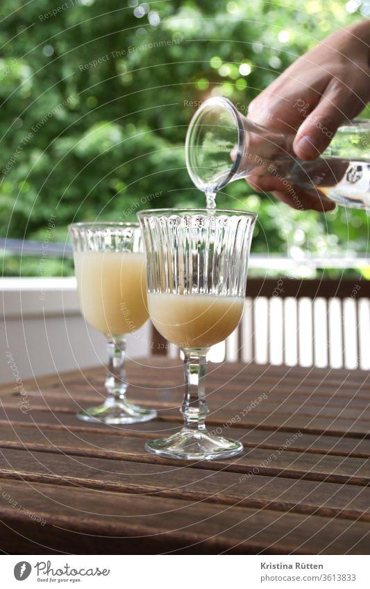 mann giesst pastis mit wasser aus einer karaffe auf aperitif getränk alkohol anis anisschnaps spirituose mischen aufgiessen mischung milchig typisch klassisch