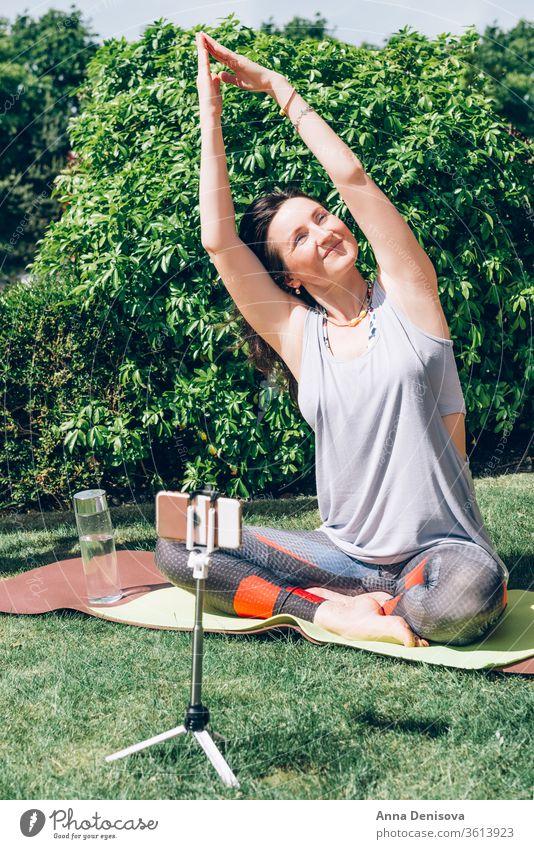 Frau macht Yoga im Garten online Smartphone psychische Gesundheit Wellness einfache Freuden Meditation Entfernte Workouts Von zu Hause aus trainieren