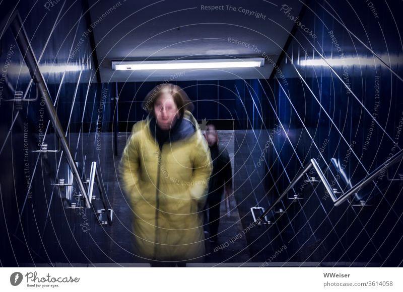 U-Bahn Übergang, Frau wird von Mann verfolgt Tunnel Treppe dunkel verfolgen Angst Furcht Unsicherheit Gefahr unsicher ängstlich gruselig gefährlich blau