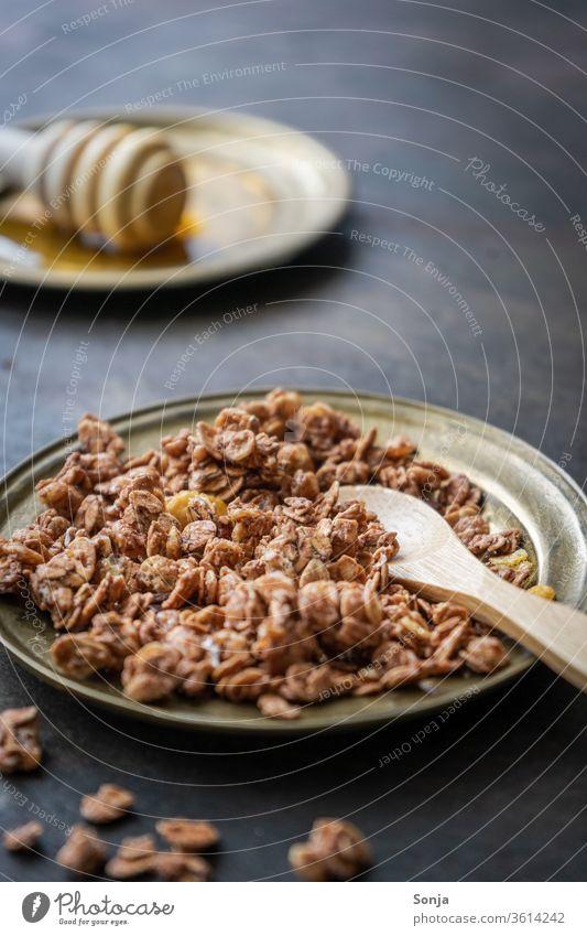 Granola auf einem goldenen Teller mit einem Holzlöffel, rustikaler Hintergrund Müsli Schokolade Nuss Dessert Frühstück Lebensmittel Ernährung Getreide frisch