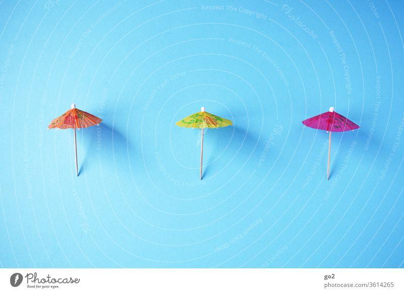 3 Sonnenschirme auf Abstand Sommer Urlaub Papierschirmchen abstand halten Abstandsregel corona orange gelb pink Infektionsgefahr Schutz Gesundheit Schützen