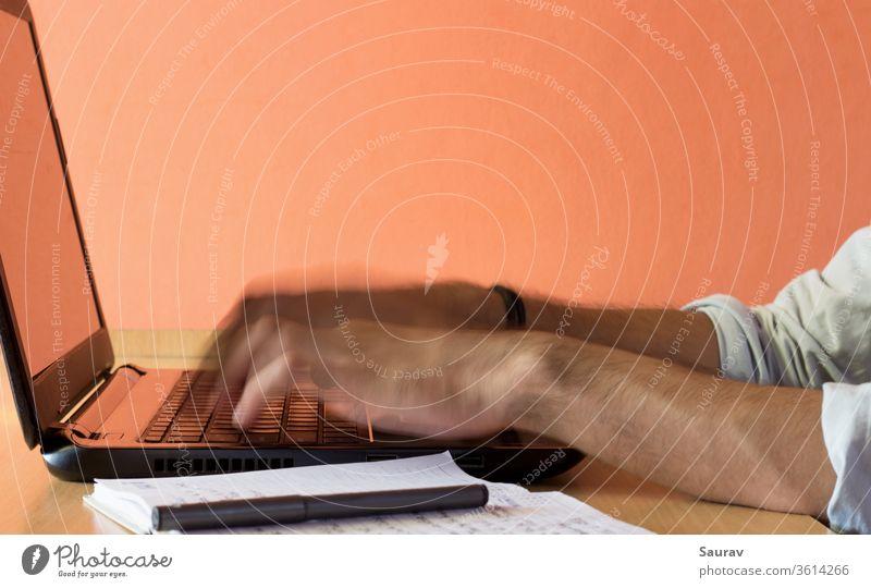 Eine bewegungsunscharfe Nahaufnahme der Finger eines jungen Erwachsenen, der von zu Hause aus auf einem Laptop arbeitet, der auf einem Holztisch neben einem Stift und einem Notizblock aufbewahrt wird.