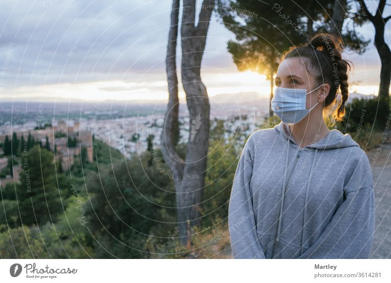 Junges Mädchen schaut mit einer Maske beim Covid, Verschmutzung durch die Sonne im Hintergrund, über der Stadt der Alhambra, Spanien. Sommerlicher Sonnenuntergang mit Sonnenlicht.