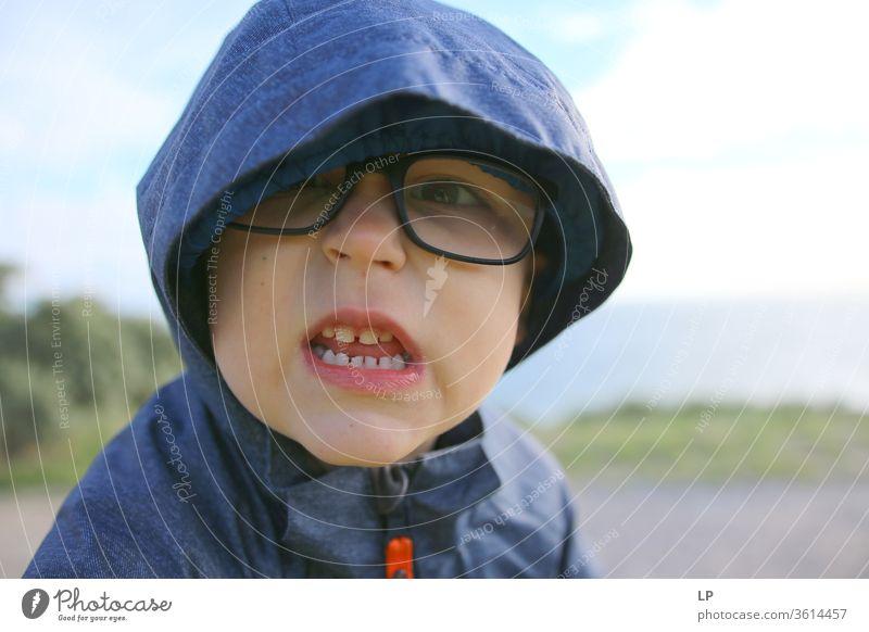 wütender kleiner Junge Zähne zeigend Gebiss Zahnarzt Biss Nahaufnahme Zahnpflege Zahnmedizin gefährlich verärgert kämpfen Feindseligkeit Kapuze Brille Blick