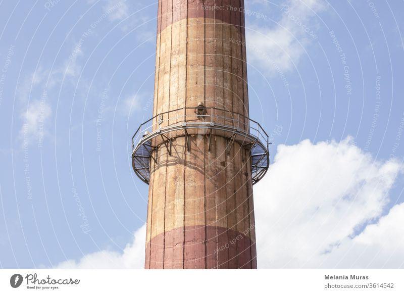 Teil eines alten Hochindustrieschornsteins mit Metallkonstruktion. Nahaufnahme. Blauer Himmel im Hintergrund. Alte Industriearchitektur. Kohleindustrie.