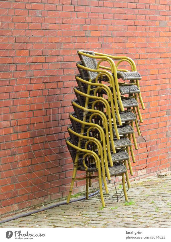 Acht gesicherte übereinander gestapelte Korbstühle vor einer rot-braunen Ziegelwand Stuhl Stapel Restaurant coronakrise Menschenleer Außenaufnahme Gastronomie