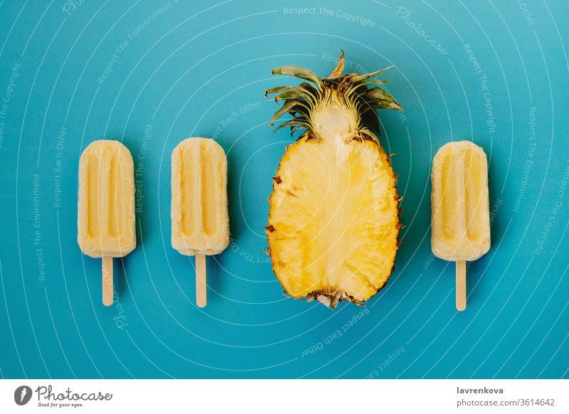 Tropischer Flachschlag aus drei veganen Eis am Stiel und der Hälfte einer reifen Ananas auf cyanfarbenem Hintergrund saisonbedingt Sommer kalt Dessert