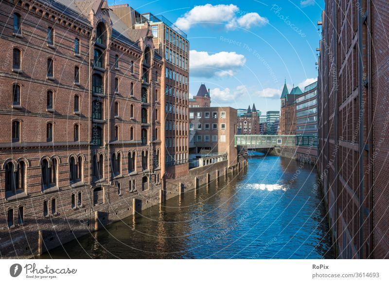 Blick über einen Kanal in der hamburger Speicherstadt. Hafen Lagerhaus storehouse urban Hamburg Elbe Brücke Gebäude Architektur Fluss Licht Ebbe Handel Gewerbe