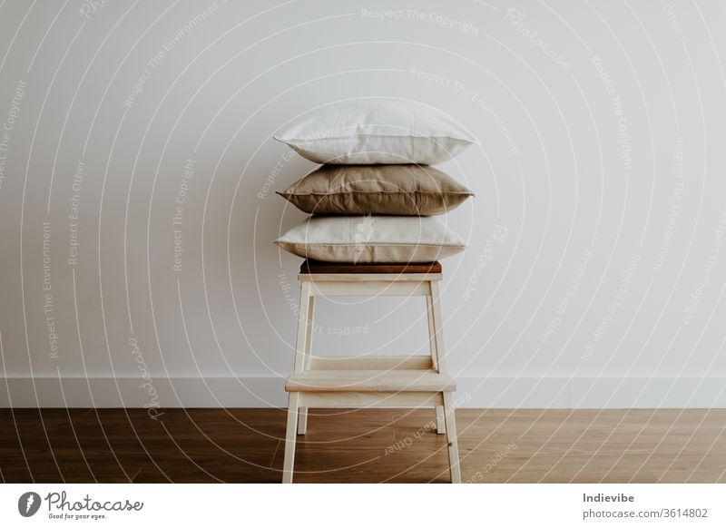 Hocker mit Kissen in einem leeren Raum Möbel sehr wenige Appartement Hintergrund beige braun Stuhl Zeitgenosse gemütlich gemütliches Zuhause Innenbereich Dekor