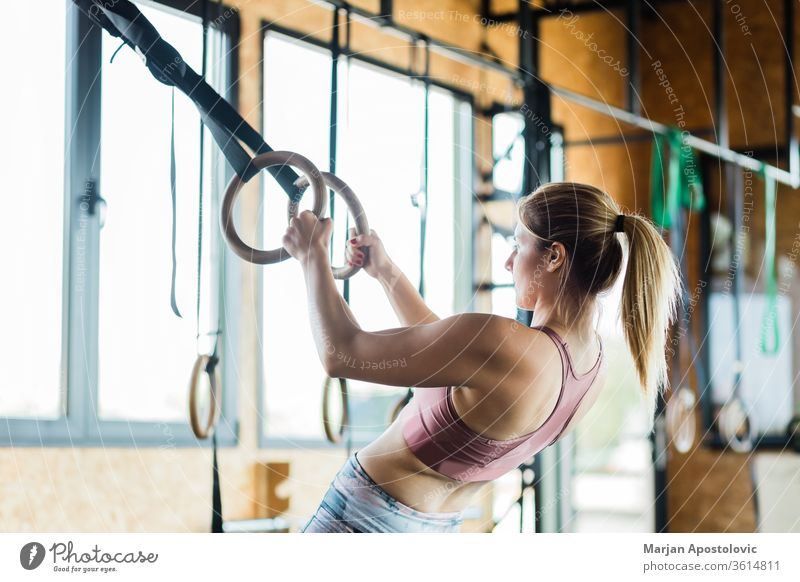 Junge sportliche Frau trainiert auf Gymnastikringen muskulös Waffen Beteiligung im Innenbereich passen Fitness Sport zäh Ausdauer eine Menschen fokussiert Kraft