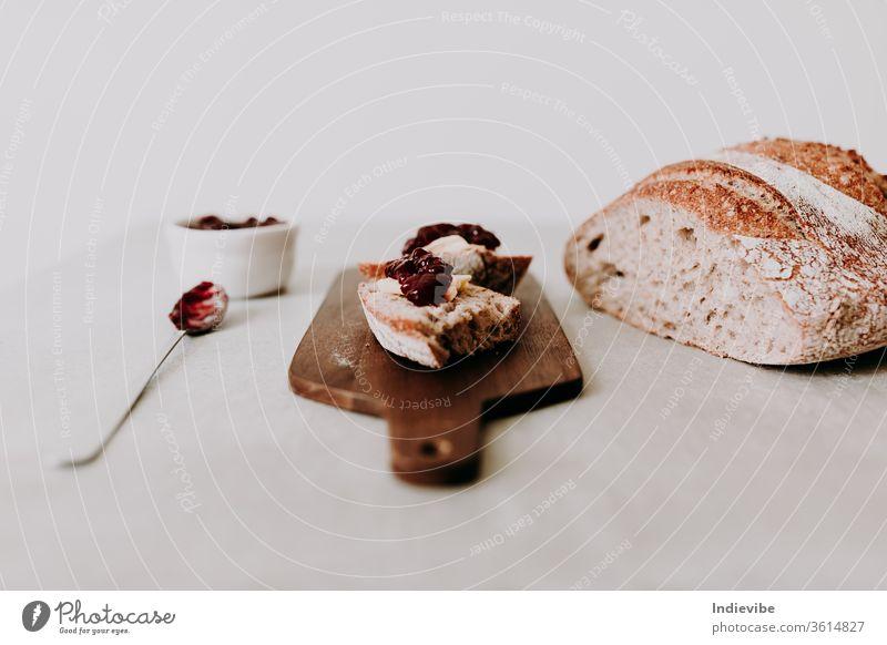 Zwei Scheiben hausgemachtes Bio-Sauerteigbrot mit Butter und Himbeermarmelade auf einem Holzschneidebrett mit Löffel und Laib Brot und Serviette frisch Vollkorn