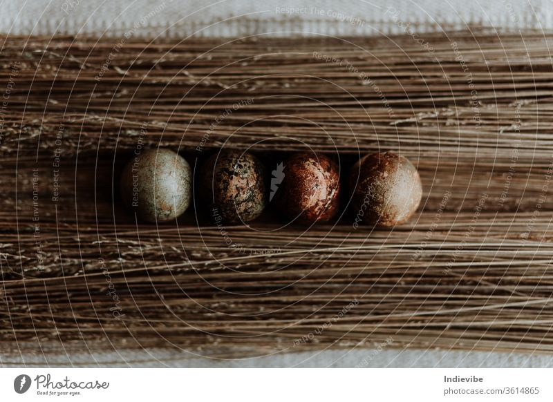 Vier verschiedene Muster natürlich gefärbtes Osterei-Osterdekor auf Strohhintergrund auf einer Leinentischdecke Ostern Ei Dekoration & Verzierung organisch