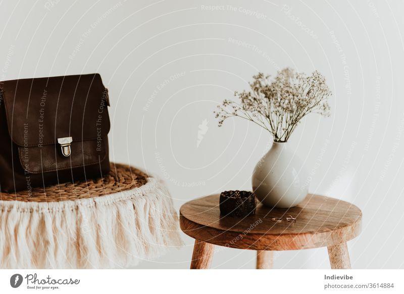 Details zur Zusammensetzung des Zubehörs für Frauen und Mädchen. Weiße Blume in einer kleinen Keramikvase mit Kupferarmband und goldenen Ringen und Ledertasche auf einem hölzernen Beistelltisch an einer weißen Wand in einem hellen Raum.