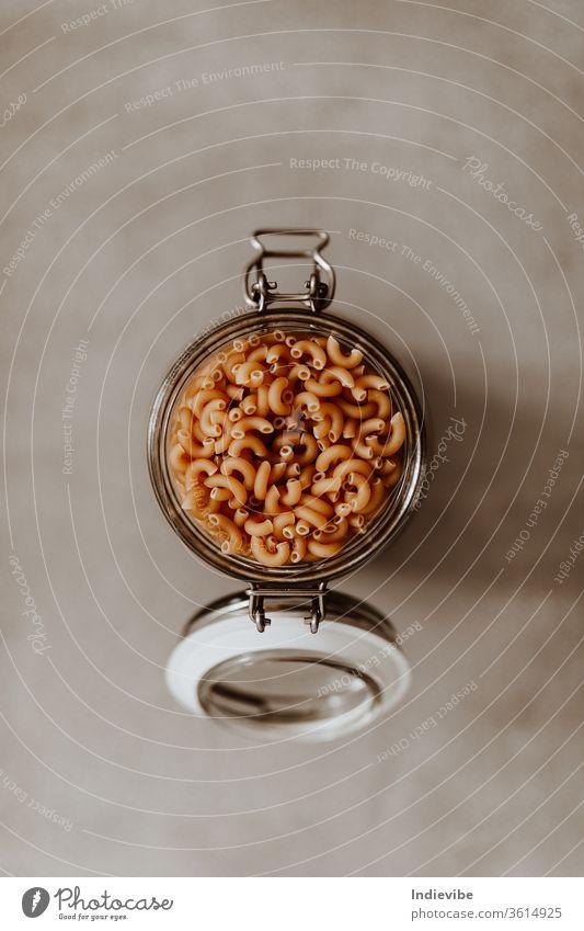 Nahaufnahme eines mit ungekochten Nudeln gefüllten Glasbehälters auf grauem Hintergrund Spätzle luftdicht Container Grundlagen Masse Vorratskammer