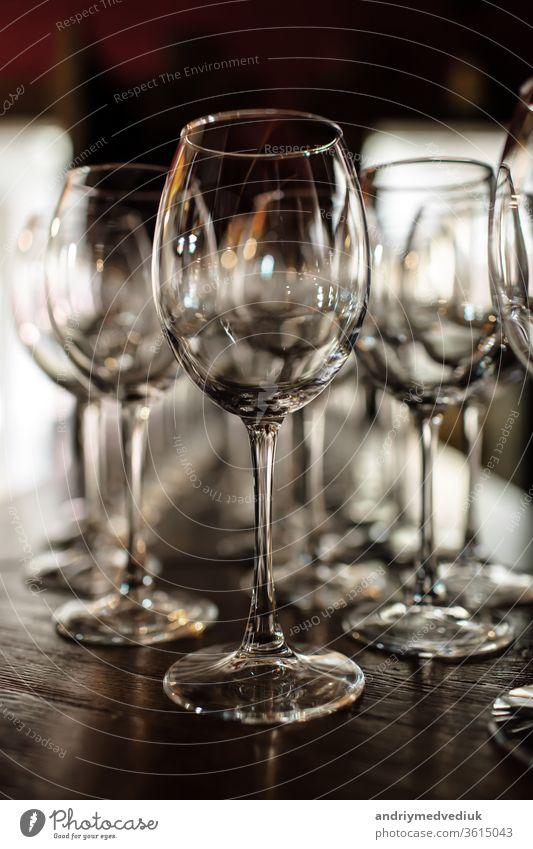 leere Weingläser. Schöne neue Gläser für Wein aus Glas stehen in gleichmäßigen Reihen auf einem Holztisch in einem Restaurant. selektiver Fokus Alkohol Bar