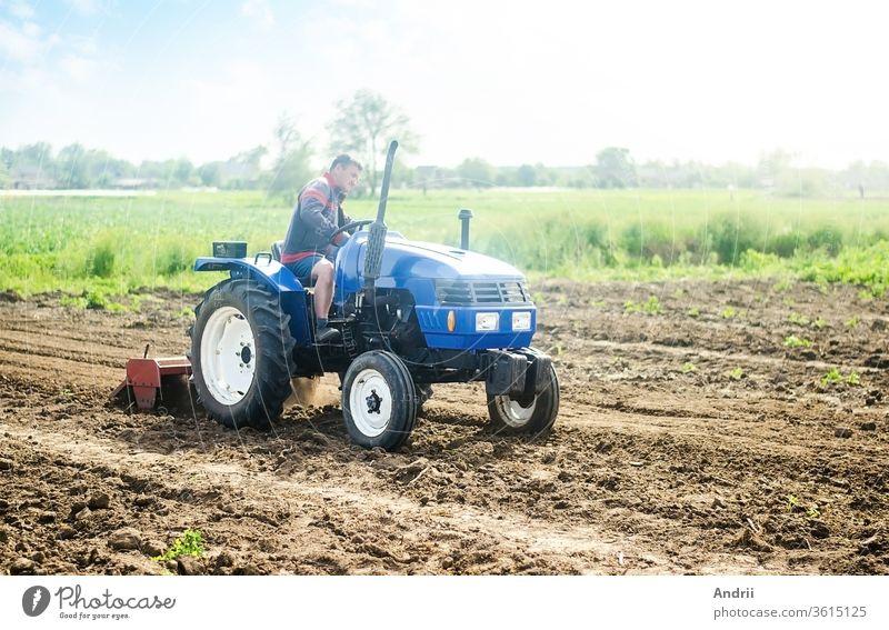 Ein Landwirt auf einem Traktor arbeitet auf dem Feld. Anbau von Feldfrüchten in einem kleinen landwirtschaftlichen Familienbetrieb. Unterstützung kleiner Unternehmen. Landwirtschaft und Ackerbau. Ausrüstung für die Anbautechnik. Lebensmittelproduktion