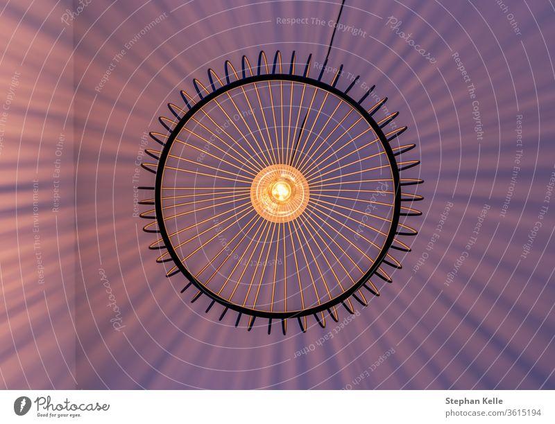 Geometrisch angeordnete Lichtstrahlen einer Lampe, die genau senkrecht von unten fotografiert wurde. Wand gestreift abstrakt modern natürlich überschatten