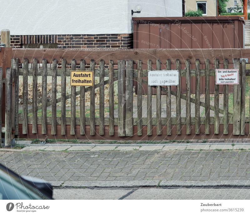 Ausfahrt freihalten - mehrere Schilder an Tor aus Holz vor der Ausfahrt eines Grundstücks und Garagentor Einfahrt Bürgersteig Botschaft Parkverbot Auto eng