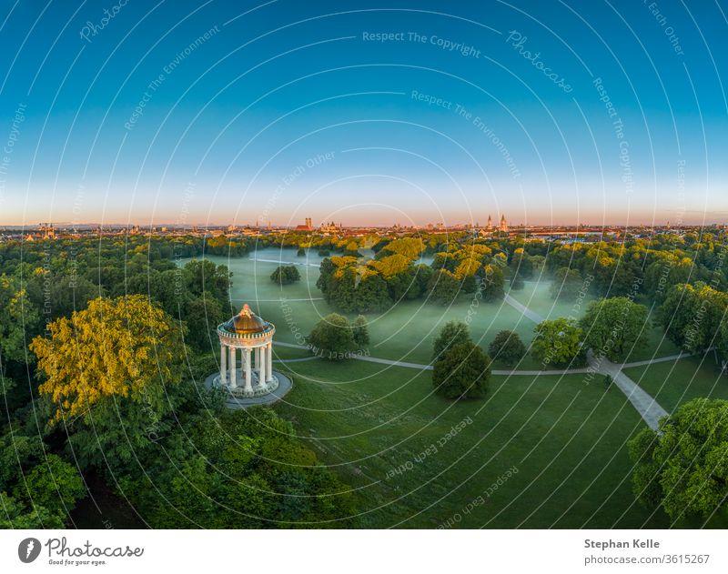 Wunderschöne Luftaufnahme über dem Englischen Garten der bayerischen Landeshauptstadt München am frühen Morgen bei Nebel im grünen Park. neblig Baum Bayern
